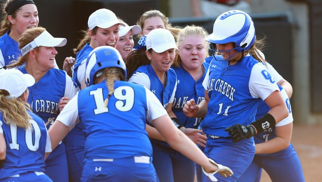 Oak Creek pitcher Becca Oleniczak (#11) gets a warm welcome at home plate after hitting a solo home run in the fourth inning.