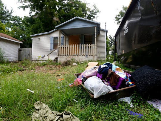 A dumpster sits in the yard of an abandoned house with trash scattered around the yard. Houses like this are considered chronic nuisance properties by the city.