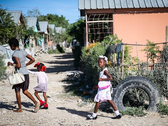 A mother and children walk past a row of homes on their way to Sunday church service in Onaville.