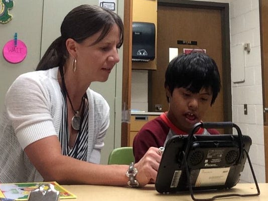 Becca Hoke, a speech and language therapist and assistant technology consultant, works with a student at the Franklin Learning Center.