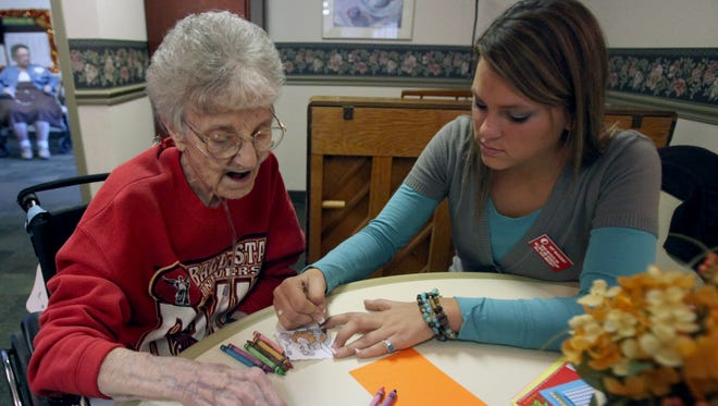 A graduate student from Ball State University helps a resident of The Waters of Yorktown in this Star Press file photo.