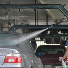 An employee cleans cars in a car wash in Alhambra, Calif.