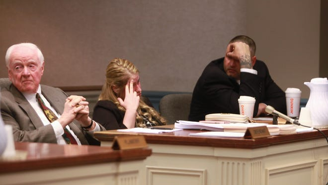 Christopher Banta, at right, and his wife, Sondra Gannon, attempt to conceal their faces in state Superior Court in Sussex County in May. Gannon's attorney, George Daggett, is seen to the left.