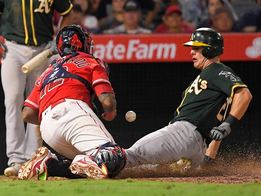 Oakland Athletics' Mark Canha, right, steals home as Los Angeles Angels catcher Martin Maldonado misses the throw during the sixth inning of a baseball game, Saturday, Aug. 5, 2017, in Anaheim, Calif. (AP Photo/Mark J. Terrill)
