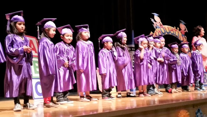 Teacher Paula Romero stands with her Pre-Kindergarten students from Mescalero Apache Elementary as they prepare to graduate May 3 in their caps and gowns.