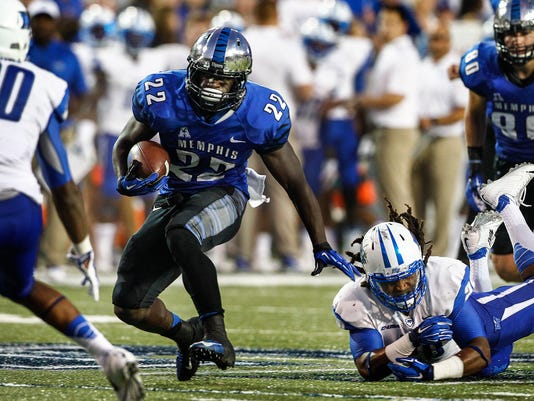 Memphis running back Doroland Dorceus, center, scrambles past Middle Tennessee State's Christian Henry, right, on his way to a touchdown during first half action of their NCAA college football game in Memphis, Tenn. on Saturday, Sept. 20, 2014. (AP Photo/The Commercial Appeal, Mark Weber)