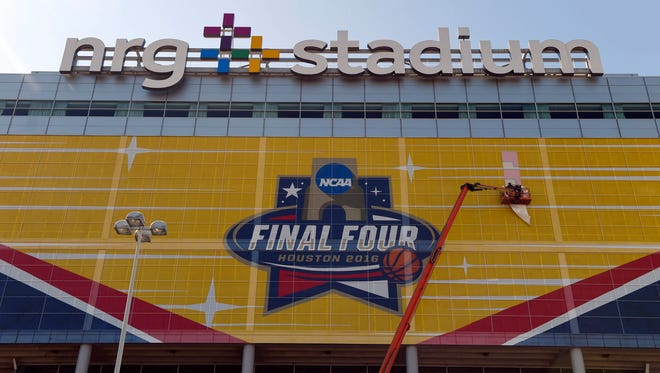 A worker applies signage to the side of NRG Stadium in preparations for the 2016 Final Four in Houston.