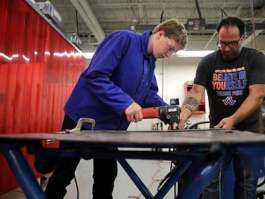 John Gillis, a sophomore, uses a nibbler to cut through metal with the help of Bob Lemkey, an instructor at Appleton Technical Academy, Sept. 25 in Appleton.