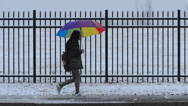 A woman uses her umbrella to keep the snow off while walking along Ridge Road in North Arlington Tuesday morning, Jan. 30, 2018.