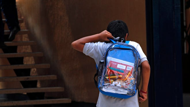 A secondary school student walks carrying his new transparent backpack.