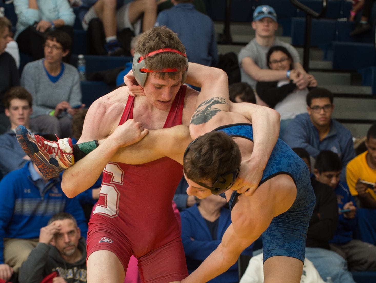 Smyrna's Chase Archangelo holds the leg of Dover's Nicholas Lee in the 145 pound championship match at the Henlopen Conference wrestling tournament at Sussex Central High School.