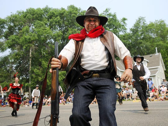 Wild West re-enactment actors run toward the crowd during their shootout performance during the Fourth of July Parade on Saturday in St. Joseph.