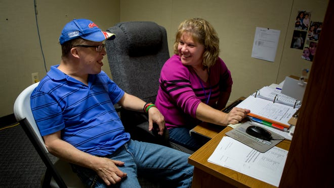 Denise Kish, a job coach and support worker, talks with Robert Wilton, of Marysville, about his dog biscuit company, BW's Biscuits, Wednesday, Sept. 28, 2016, at Community Enterprises in Port Huron.