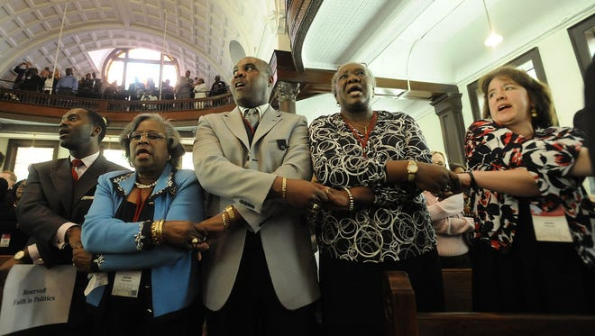 """People in this file photo hold hands and sing """"We Shall Overcome"""" during the 45th annual commemoration of Bloody Sunday at Brown Chapel AME Church in Selma. Guy Carawan, a folk singer and social-justice advocate credited with turning the song into a unifying anthem of the 1960s civil rights movement, has died at 87."""