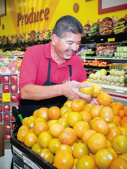 Jett Loe — Sun-News 27-year veteran of SaveMart, Produce Manager David Mendoza, arranges oranges for sale on Tuesday.