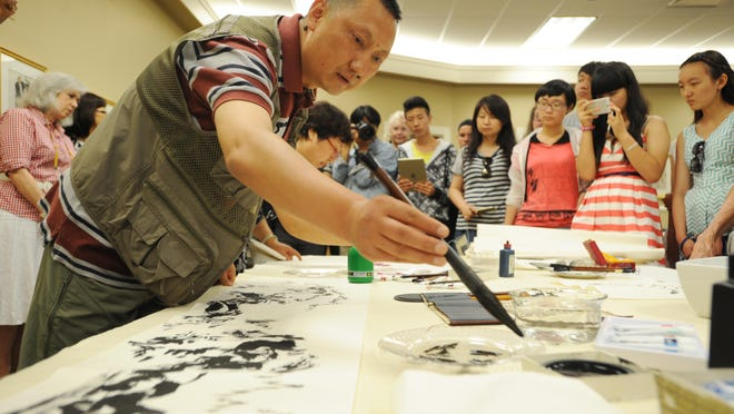 Zhe Qi paints during a demonstration of Chinese art Tuesday at the Zanesville Museum of Art.