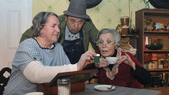 """Opal show's Rosie her tiny Bible as Norman watches from behind in a scene from the 2010 Mansfield Playhouse production of """"Opal's Baby"""". (L-R) Others in the scene are Suzanne Allen, Gordon Wendling, and Millie Leverton (Rosie). The Playhouse has announced its lineup for the 2019-2020 season."""