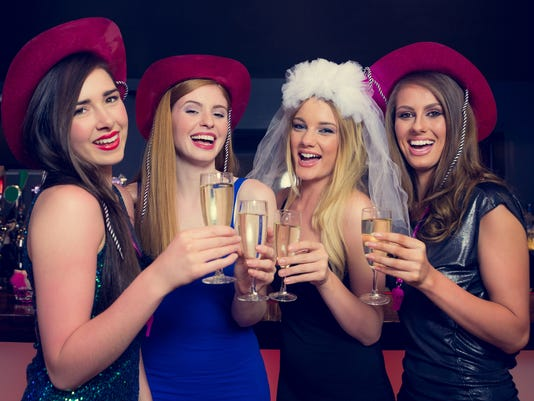 Laughing friends clinking champagne glasses at a hen night