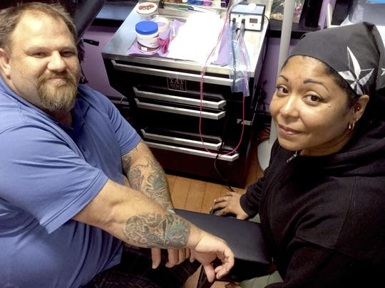 Dale and Clarissa Wills show off a battlefield cross tattoo Clarissa created in memory of friend Sgt. Krisna Nachampassak, who died in Iraq in 2004. The couple owns and operates Beauty Marks in Port Royal, S.C.