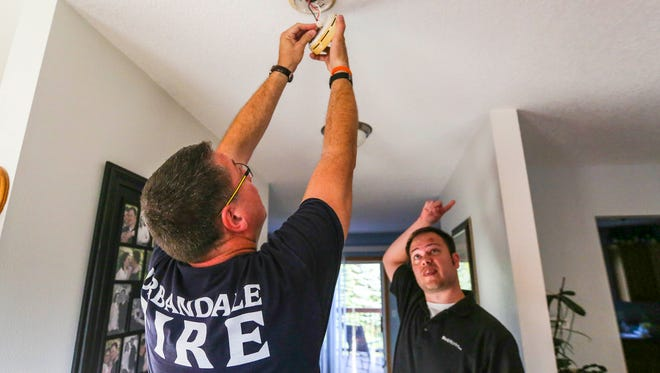 Urbandale fireman Kyle Bissel checks the smoke detector of Justin Rasmussen's home. As part of fire prevention month, the Urbandale Fire Department is teaming up with Papa John's pizza to deliver pizzas to unsuspecting customers Wednesday, Oct. 7, 2015. Once there, firefighters will offer to inspect homes and check smoke detectors.