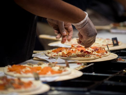 Toppings are placed on pizzas before being placed in