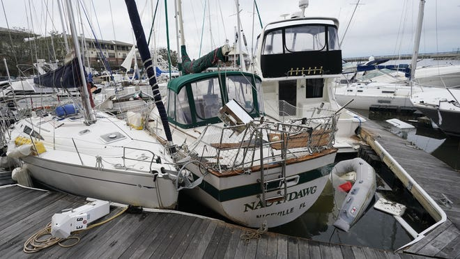 Storm damaged boats sit at the dock in a marina, Thursday, Sept. 17, 2020, in Pensacola, Fla. Rivers swollen by Hurricane Sally's rains threatened more misery for parts of the Florida Panhandle and south Alabama on Thursday, as the storm's remnants continued to dump heavy rains inland that spread the threat of flooding to Georgia and the Carolinas.