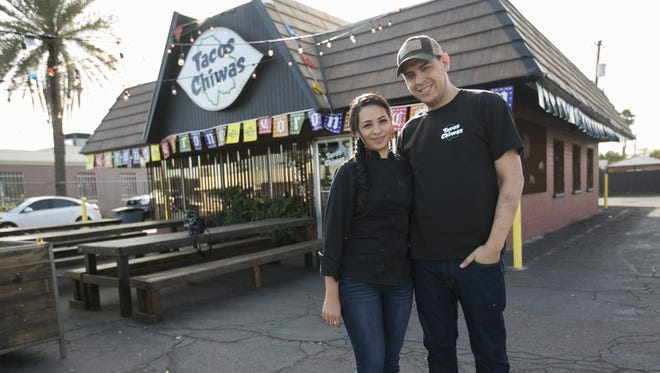Husband and wife Nadia Holguin (left) and Armando Hernandez (right) stand in front of their restaurant Tacos Chiwas in Phoenix, Arizona, on Tuesday, Feb. 2, 2016.