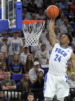 A Florida Gulf University basketball player dunks during a game.