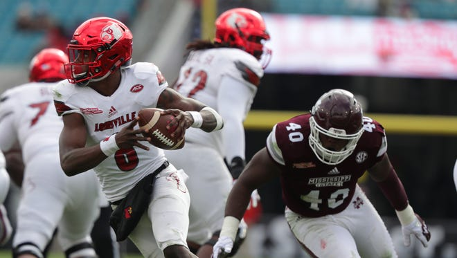 Louisville's Lamar Jackson scrambles to avoid a sack in the second half of the TaxSlayer Bowl against Mississippi State. Dec. 30, 2017