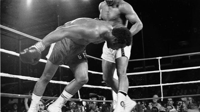 """From Oct. 30, 1974, challenger Muhammad Ali, top, watches as defending world champion George Foreman goes down to the canvas in the eighth round of their WBA/WBC championship match in Kinshasa, Zaire. The 1996 film """"When We Were Kings"""" is a documentary of the bout known as the """"Rumble In The Jungle"""" between Ali and Foreman. The fight was a cultural milestone that ran far deeper than boxing."""