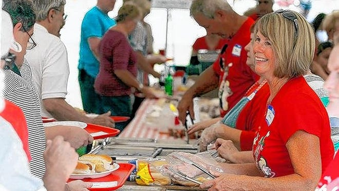 Volunteer Jana Blamble serves up bratwurst and hot dogs Aug. 1, 2014, during the St. James Brats and Crafts Festival at St. James Lutheran Church, 5660 Trabue Road in Columbus. This year's festival has been canceled because of the COVID-19 coronavirus pandemic.