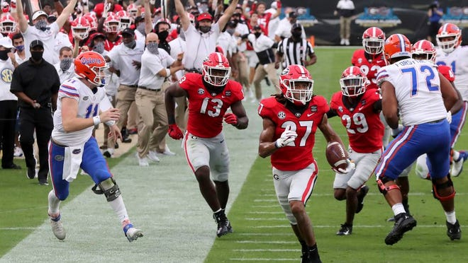 Georgia defensive back Eric Stokes (27) returns an interception for a touchdown during the second quarter of a NCAA college football, Saturday, Nov. 7, 2020, in Jacksonville, Fla.