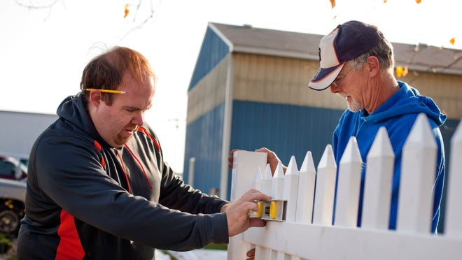 Kevin Kerbrat, of St. Clair, and Tom Thornton, of Port Huron, put up a white picket fence as part of landscaping for a new accessible path during Make a Difference Day Saturday at Community Enterprises of St. Clair County in Port Huron Township.
