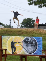 Painted by local artist Amy Peters, the American mystic and Hopkinsville native Edgar Cayce along with the upcoming solar eclipse is depicted on a bench in front of the Eclipse Headquarters in Hopkinsville Thursday, July 27, 2017.