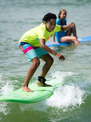 Ava Babcock-Watford rides the waves at Innerlight's surf camp at Pensacola Beach on Friday, June 29, 2018.