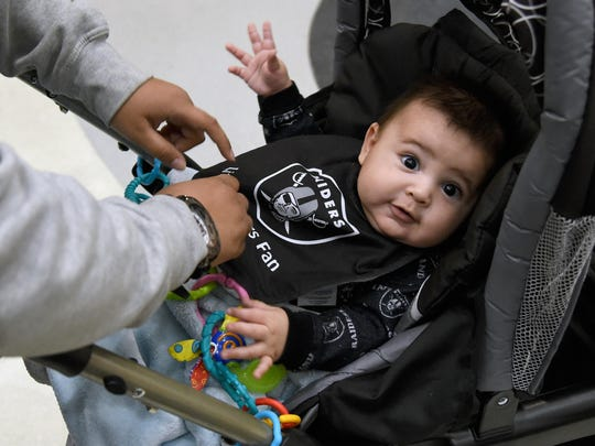 Four-month-old Delphino Rubi V of Nevada is dressed in Oakland Raiders gear as fans wait for Raiders owner Mark Davis to arrive at a Southern Nevada Tourism Infrastructure Committee meeting on April 28.