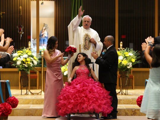 Lands are raised to bless Karizma Vargas during her quinceañera Catholic Mass at Madonna del Sasso Catholic Church.