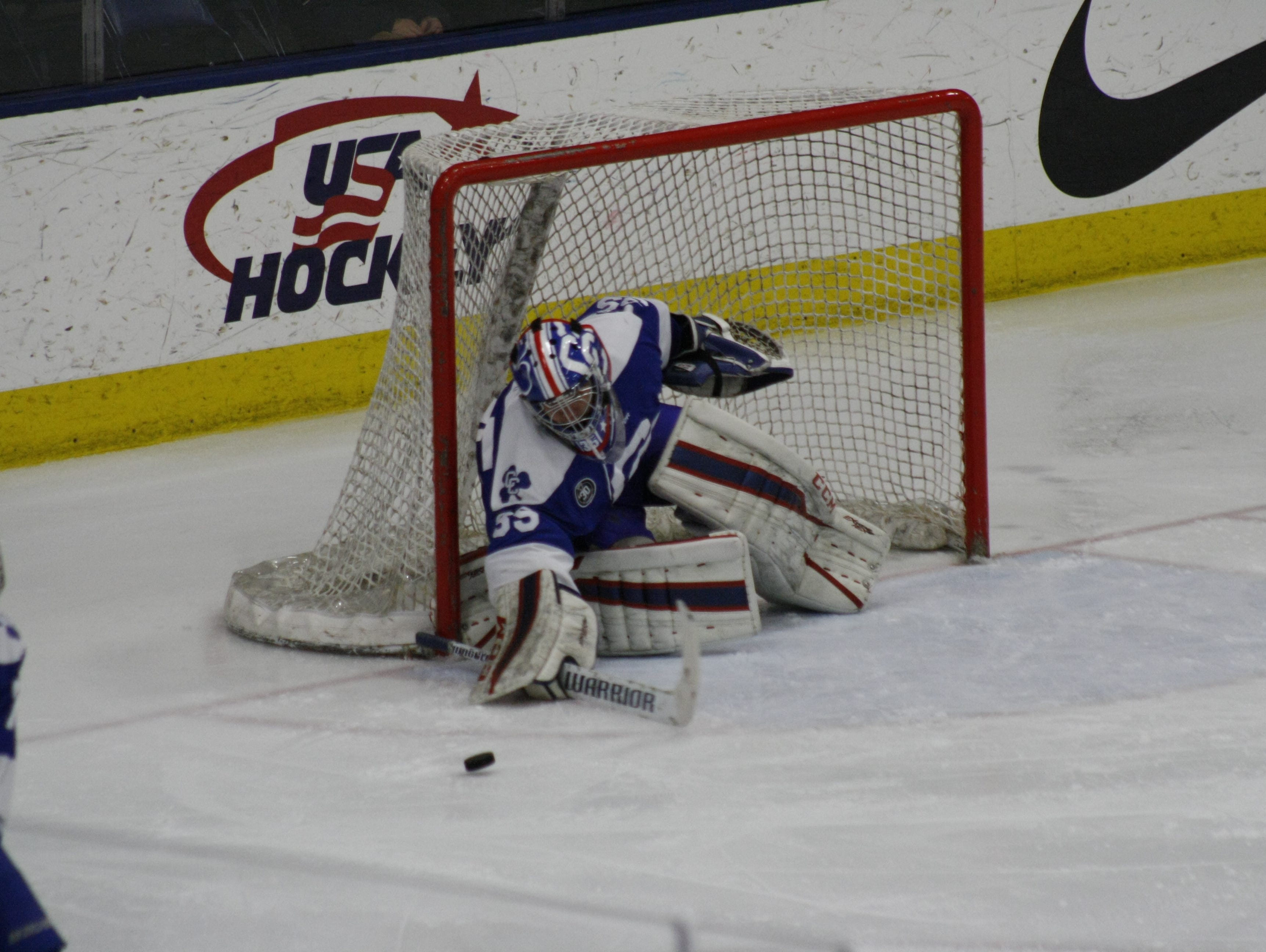 Novi Detroit Catholic Central goalie Sean Finstrom knocks away a Grandville shot during Friday's Division 1 state semifinal match at USA Hockey Arena in Plymouth.