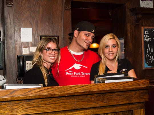 Deer Park Tavern employees wear t-shirts with the restaurant's logo in 2013. The logo was changed late last year to feature a purple raven.