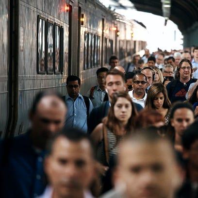 People walk along the railway platform as they arrive