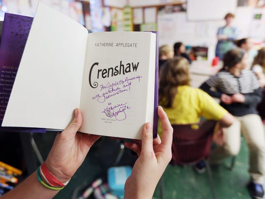 "Fifth-grader Anjolie Palmer receives a personally signed version of ""Crenshaw"" by Katherine Applegate, her favorite author, during class Wednesday, Dec. 16, 2015, at EAGLE Charter School in Salem, Ore."