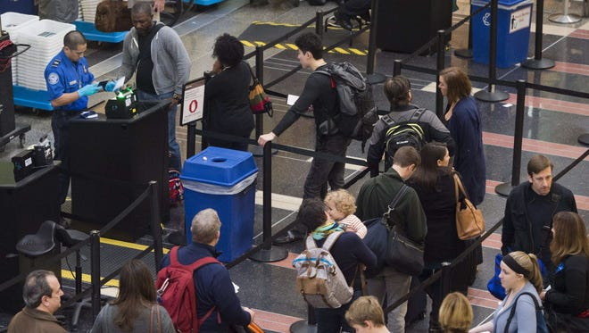 Passengers stand in line to go through a Transportation Security Administration checkpoint at Reagan National Airport in Arlington, Va., on Dec. 23, 2015.