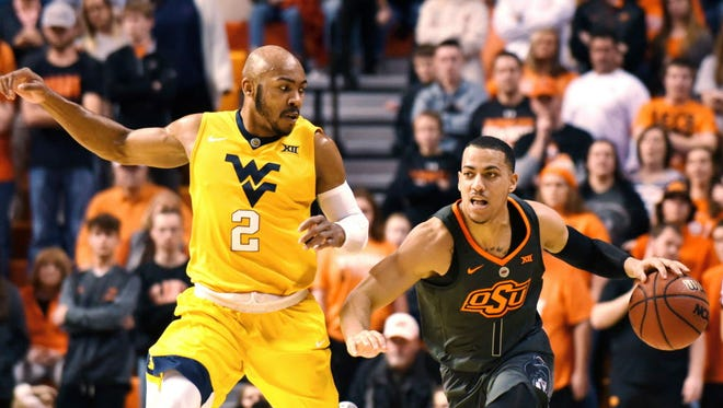 West Virginia guard Jevon Carter (2) races to catch up with Oklahoma State guard Kendall Smith (1) in the first half.