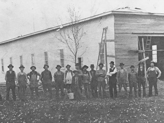 Workers pose outside an airplane shed they were building
