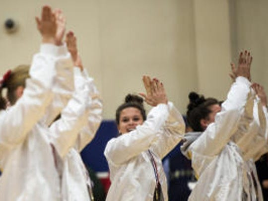 Members of the New Oxford cheerleading team perform a cheer during a February rally at their high school celebrating the Colonials' United Cheerleading Association medium varsity coed national championship
