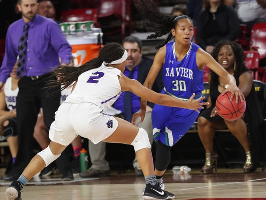Xavier's Leilani McIntosh (30) is pressured by Millennium's