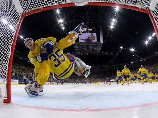 Sweden goalie Henrik Lundqvist is hugged/tackled by