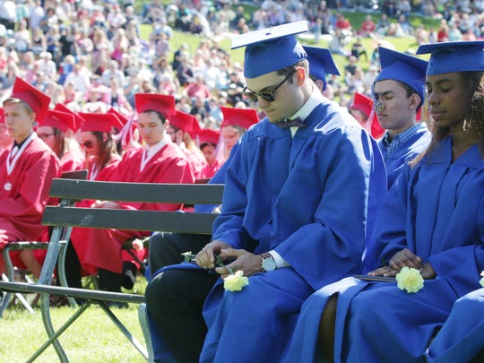 Graduates bow their head in silence for students who did not live to see graduation Sunday June 5, 2016 in Sheboygan.