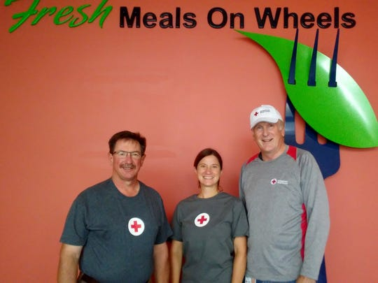 Three people from the American Red Cross stand in front of the Fresh Meals and Wheels wall logo