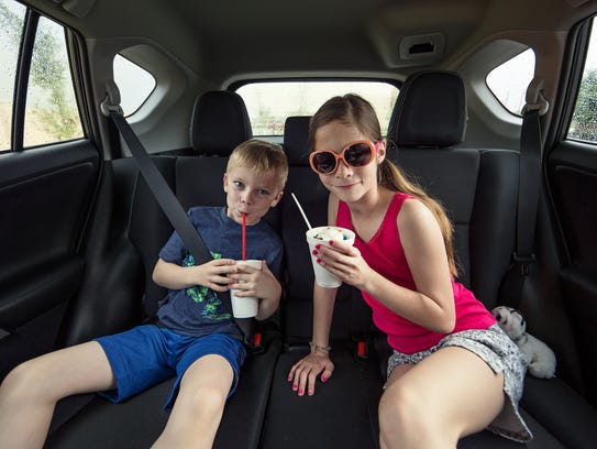 Two kids eating a fast food treat.